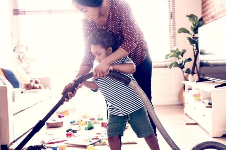 Mom vacuuming with child