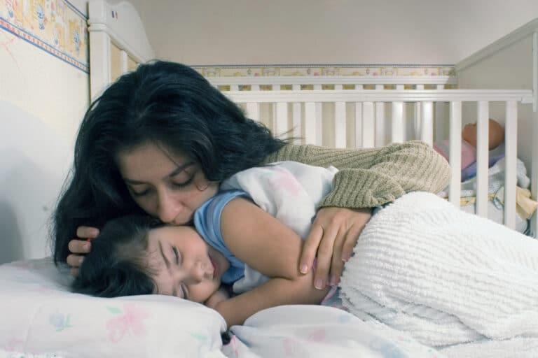 Mother kissing child goodnight