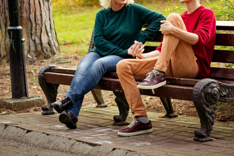 Woman and teen talking on bench