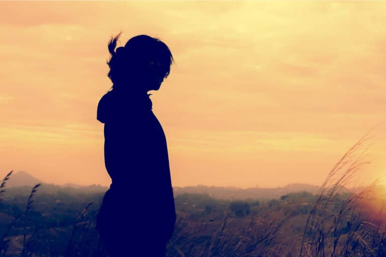 Woman standing in sunset