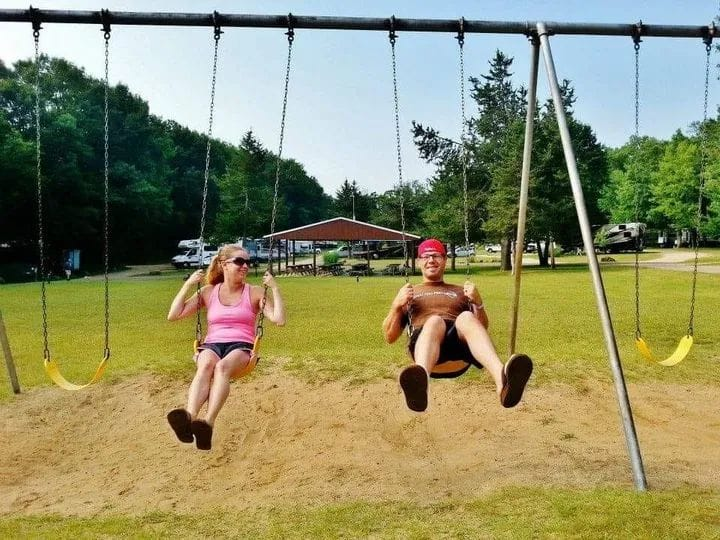 Husband and wife on swing set, color photo