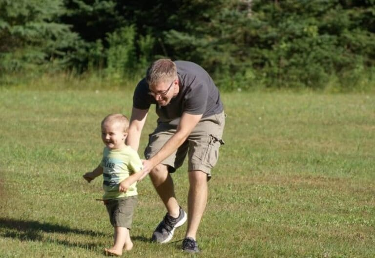 Uncle chasing child in the grass, color photo