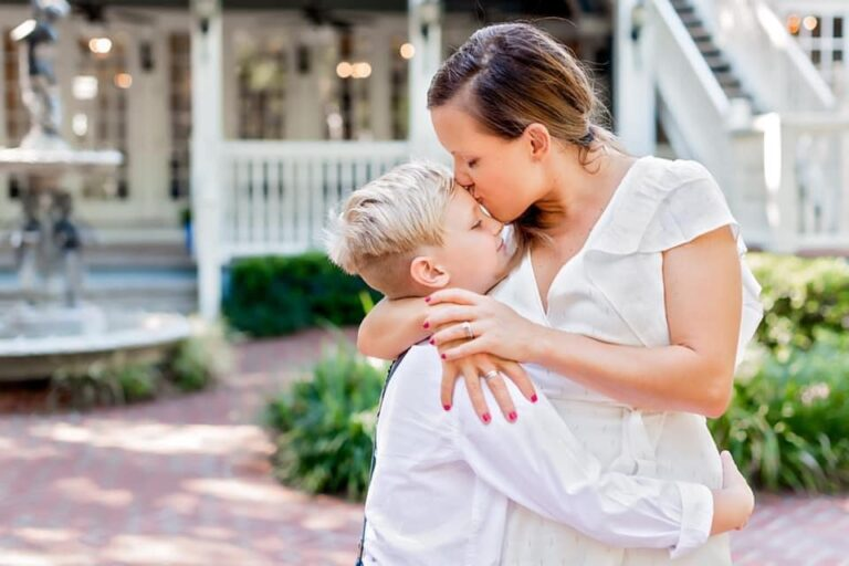 Mother kissing son on forehead, color photo