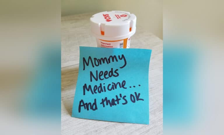 Pill bottle with sticky note reading, Mommy Needs Medicine – And That's Okay, color photo