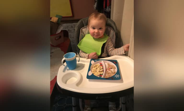 Toddler sitting in high chair, color photo