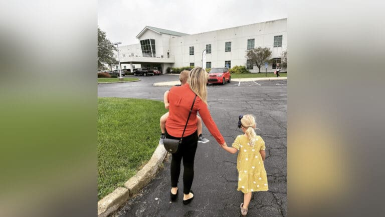 Woman holding child and the hand of another walking toward church, color photo