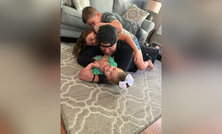 Daddy on floor, wrestling with kids, color photo