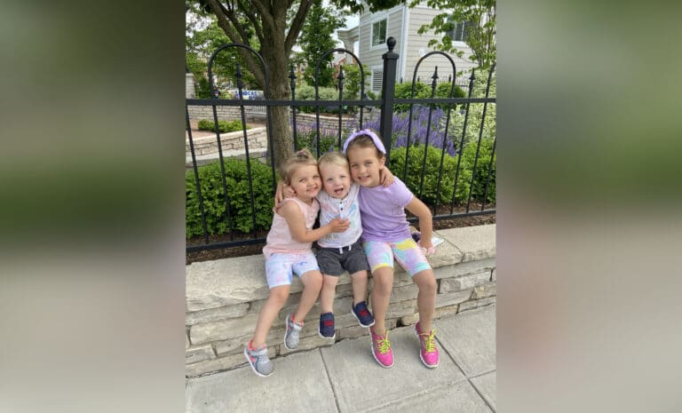 Three kids sitting on a stone wall, color photo