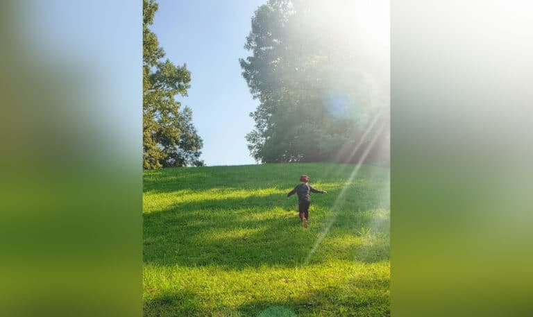 Child standing in sunlight in grassy area, color photo