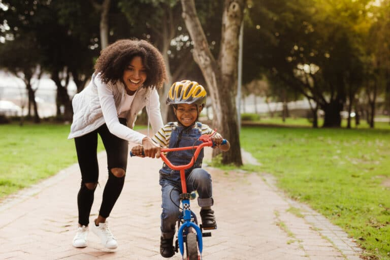 Mom helps boy learn to ride bike