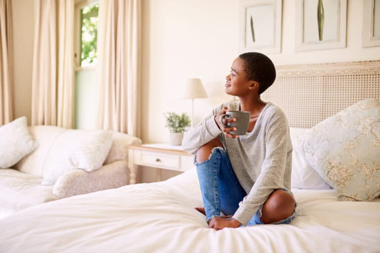 Smiling woman on bed with coffee cup