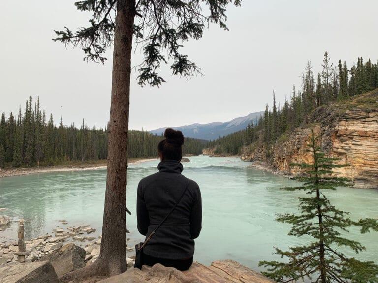 Woman sitting alone by lake