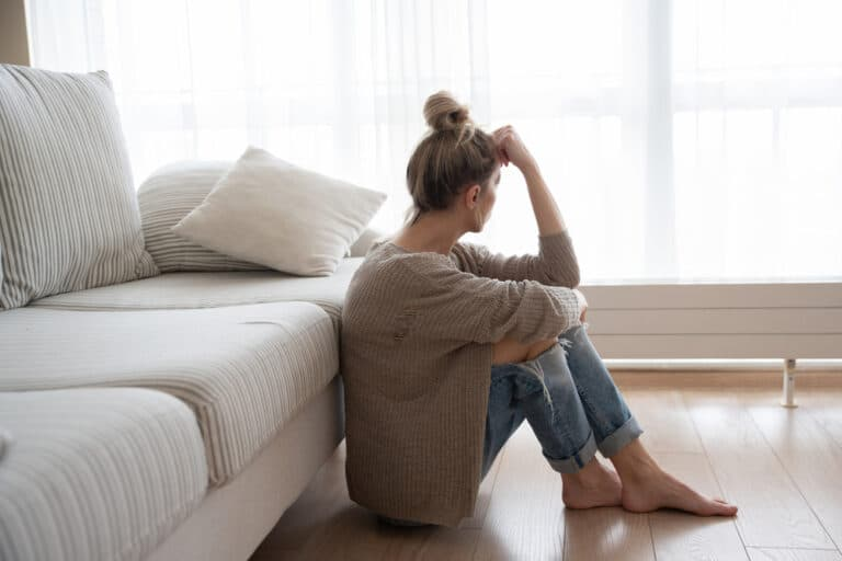 Woman sitting on living room floor