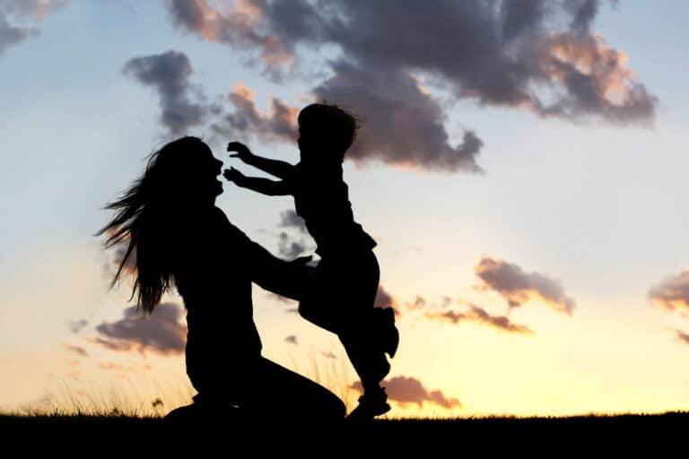 Silhouette mother hugging child
