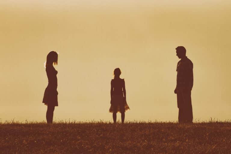 Child standing between divorced parents