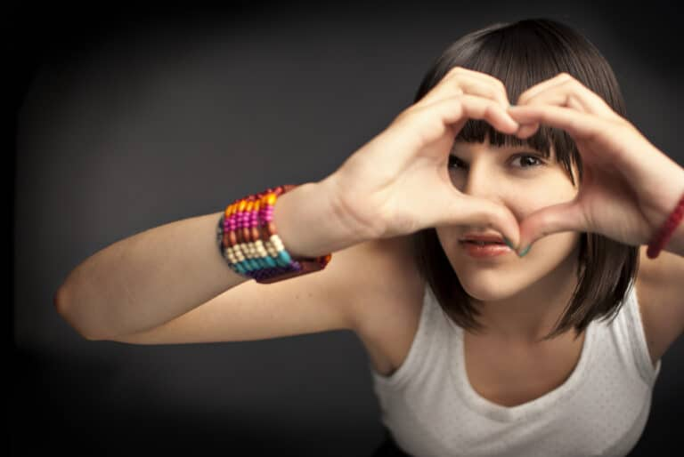 Teen girl forming heart with her hands
